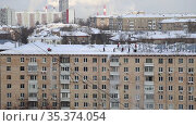 Cleaning the roof from snow in a residential area of Moscow on a sunny winter day after heavy snowfall, Russia. Стоковое видео, видеограф Владимир Журавлев / Фотобанк Лори