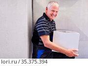Älterer Arbeiter trägt einen Karton zum Warenlager einer Fabrik oder... Стоковое фото, фотограф Zoonar.com/Robert Kneschke / age Fotostock / Фотобанк Лори