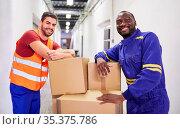 Zwei lächelnde Männer bei Ausbildung zum Lagerarbeiter in Fabrik ... Стоковое фото, фотограф Zoonar.com/Robert Kneschke / age Fotostock / Фотобанк Лори