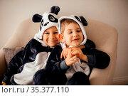 Two preschool boys are sitting in kigurumi of panda. The smiling children... Стоковое фото, фотограф Zoonar.com/OKSANA SHUFRYCH / easy Fotostock / Фотобанк Лори