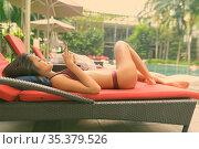 Portrait of young beautiful Asian woman relaxing by swimming pool... Стоковое фото, фотограф Zoonar.com/Toni Rantala / easy Fotostock / Фотобанк Лори