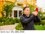 The young man has a video call outdoor using a smartphone. He is holding... Стоковое фото, фотограф Zoonar.com/OKSANA SHUFRYCH / easy Fotostock / Фотобанк Лори