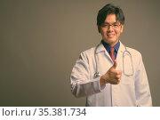 Studio shot of young handsome Asian man doctor wearing eyeglasses... Стоковое фото, фотограф Zoonar.com/Toni Rantala / easy Fotostock / Фотобанк Лори
