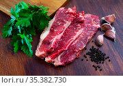 Raw marbled beef steaks with herbs and condiments. Стоковое фото, фотограф Яков Филимонов / Фотобанк Лори