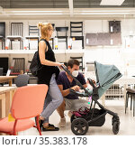 Young couple with newborn in stroller shopping at retail furniture and home accessories store wearing protective medical face mask to prevent spreading of corona virus when shops reopen. Стоковое фото, фотограф Matej Kastelic / Фотобанк Лори