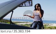African american woman talking on smartphone while standing near her broken down car on road. Стоковое видео, агентство Wavebreak Media / Фотобанк Лори