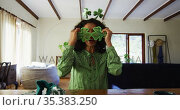 Portrait of mixed race woman wearing green glasses and costume at home. Стоковое видео, агентство Wavebreak Media / Фотобанк Лори