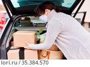 Frau mit Mundschutz lädt vollen Auto Kofferraum mit Paketen und Einkäufen. Стоковое фото, фотограф Zoonar.com/Robert Kneschke / age Fotostock / Фотобанк Лори