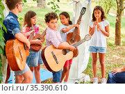 Kinder Musik Band mit Gitarren beim Talentshow Auftritt im Ferienlager... Стоковое фото, фотограф Zoonar.com/Robert Kneschke / age Fotostock / Фотобанк Лори