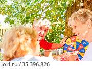 Aktive Senioren beim Dart spielen und Punkte zählen im Sommer im ... Стоковое фото, фотограф Zoonar.com/Robert Kneschke / age Fotostock / Фотобанк Лори