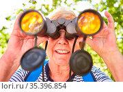 Seniorin blickt durch ein Fernglas als Konzept für Orientierung und... Стоковое фото, фотограф Zoonar.com/Robert Kneschke / age Fotostock / Фотобанк Лори