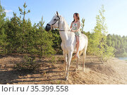 Young girl sits on a white horse without a saddle. Стоковое фото, фотограф Филатова Ирина / Фотобанк Лори