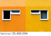 A pair of two windows on yellow and orange facade in symmetry. Стоковое фото, фотограф Zoonar.com/Andy Höch / age Fotostock / Фотобанк Лори