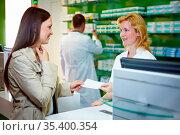 Frau mit einer Erkältung löst Rezept in einer Apotheke ein. Стоковое фото, фотограф Zoonar.com/Robert Kneschke / age Fotostock / Фотобанк Лори