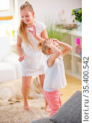 Zwei Kinder spielen zu Hause im Wohnzimmer und fangen Seifenblasen. Стоковое фото, фотограф Zoonar.com/Robert Kneschke / age Fotostock / Фотобанк Лори