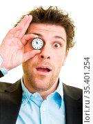 Junger Mann im Anzug hält eine Taschenuhr vor sein Auge. Стоковое фото, фотограф Zoonar.com/Robert Kneschke / age Fotostock / Фотобанк Лори