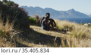 African american man cross country running in by the coast sitting and taking a break. Стоковое видео, агентство Wavebreak Media / Фотобанк Лори