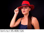 Studio shot of mature beautiful woman wearing red fedora hat against... Стоковое фото, фотограф Zoonar.com/Toni Rantala / easy Fotostock / Фотобанк Лори