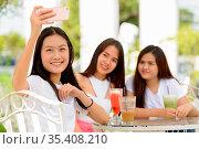 Portrait of three young beautiful Asian women as friends together... Стоковое фото, фотограф Zoonar.com/Toni Rantala / easy Fotostock / Фотобанк Лори