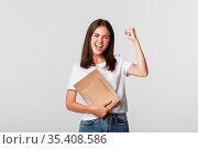 Rejoicing smiling woman holding notebooks and fist pump cheerful,... Стоковое фото, фотограф Zoonar.com/Phongthorn Hiranlikhit / easy Fotostock / Фотобанк Лори