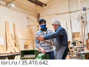 Handwerker Senior und Lehrling in Ausbildung in Werkstatt mit Mundschutz... Стоковое фото, фотограф Zoonar.com/Robert Kneschke / age Fotostock / Фотобанк Лори