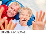 Fröhliches Rentner Senioren Paar hat Spaß beim Zelten und winkt in... Стоковое фото, фотограф Zoonar.com/Robert Kneschke / age Fotostock / Фотобанк Лори