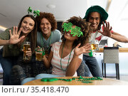 Portrait of diverse group of happy friends celebrating st patrick's day holding beers and waving. Стоковое фото, агентство Wavebreak Media / Фотобанк Лори
