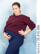 Excited brunette pregnant woman in brown cardigan and blue skirt touching belly on background. Стоковое фото, фотограф Кекяляйнен Андрей / Фотобанк Лори