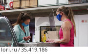 Two caucasian women wearing face masks talking at reception of gym one filling in form. Стоковое видео, агентство Wavebreak Media / Фотобанк Лори