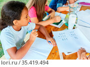 Kinder lernen Rechnen im Nachhilfe Unterricht im Ferienkurs der Sommerschule. Стоковое фото, фотограф Zoonar.com/Robert Kneschke / age Fotostock / Фотобанк Лори