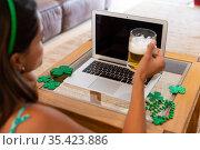Caucasian woman celebrating st patrick's day making video call using laptop holding beer. Стоковое фото, агентство Wavebreak Media / Фотобанк Лори