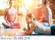 group of women resting on yoga mats at studio. Стоковое фото, фотограф Syda Productions / Фотобанк Лори