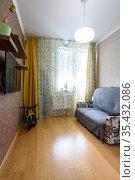 Интерьер небольшой скромной комнаты с диваном и телевизором на стене. Редакционное фото, фотограф Иванов Алексей / Фотобанк Лори