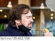 Mann mit Maske am Kinn wegen Covid-19 beim Burger essen im Snack ... Стоковое фото, фотограф Zoonar.com/Robert Kneschke / age Fotostock / Фотобанк Лори