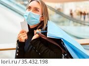 Kundin mit Maske wegen Covid-19 Pandemie beim Shopping hält ihre ... Стоковое фото, фотограф Zoonar.com/Robert Kneschke / age Fotostock / Фотобанк Лори
