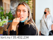 Ängstliche Frau mit Mundschutz am Kinn wegen Covid-19 Pandemie im Cafe. Стоковое фото, фотограф Zoonar.com/Robert Kneschke / age Fotostock / Фотобанк Лори