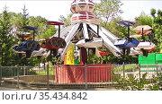 Amusement park carousel  Карусель в парке развлечений для детей и взрослых в виде летающих объектов, автомобилей. Проводится проверка перед началом сезона. Редакционное видео, видеограф Владимир Ушаров / Фотобанк Лори