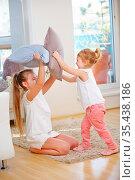 Geschwister machen zusammen eine Kissenschlacht zu Hause. Стоковое фото, фотограф Zoonar.com/Robert Kneschke / age Fotostock / Фотобанк Лори