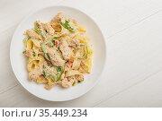 Паста Феттучини с курицей в сливочном соусе на белой тарелке.Вид сверху. Стоковое фото, фотограф Galina Oleksenko / Фотобанк Лори