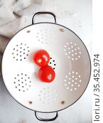 Red tomatoes in a white colander on a white background. Стоковое фото, фотограф Марина Володько / Фотобанк Лори