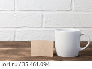 Household utensils, a white cup stands on a shelf on a wooden table against the background of a kitchen stone brick wall of a milky shade, the concept of clean dishes. Стоковое фото, фотограф Светлана Евграфова / Фотобанк Лори