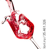 Red wine is pouring into a glass goblet on a white background. Стоковое фото, фотограф Restyler Viacheslav / Фотобанк Лори