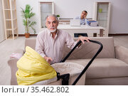 Retired grandfather looking after newborn at home. Стоковое фото, фотограф Elnur / Фотобанк Лори