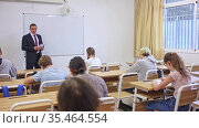 Group of students listening attentively to teacher explaining material in classroom. Стоковое видео, видеограф Яков Филимонов / Фотобанк Лори