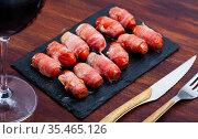 Traditional Spanish tapas - rolled bacon at black plate. Стоковое фото, фотограф Яков Филимонов / Фотобанк Лори