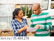 Woman and man discussing documents on farm near car. Стоковое фото, фотограф Яков Филимонов / Фотобанк Лори