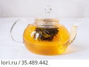 Чай заваривается в стеклянном чайном чайнике на белом фоне. Стоковое фото, фотограф Кузин Алексей / Фотобанк Лори