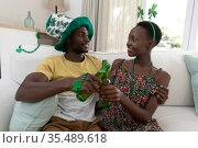 African american couple wearing st patrick's day costumes smiling and holding glasses of beer. Стоковое фото, агентство Wavebreak Media / Фотобанк Лори