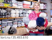 Aged woman enjoying purchased home textiles in textile shop. Стоковое фото, фотограф Яков Филимонов / Фотобанк Лори