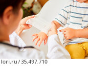 Kinderarzt wickelt Verband um Handgelenk von Kind bei Verstauchung... Стоковое фото, фотограф Zoonar.com/Robert Kneschke / age Fotostock / Фотобанк Лори